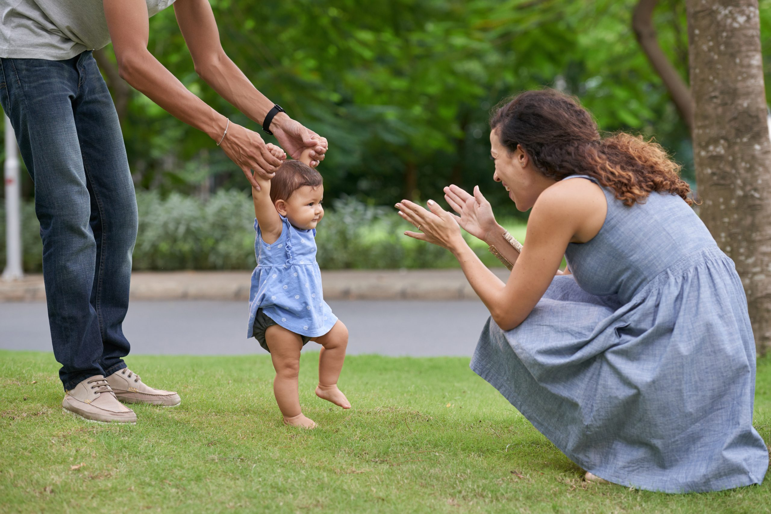 Baby holding onto dad's hands attempting to walk to mom outside in the grass