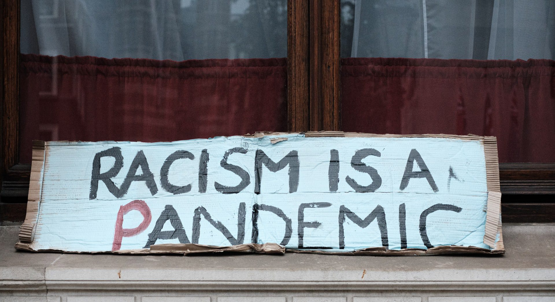 """black and white sign written on cardboard that says """"racism is a pandemic"""""""