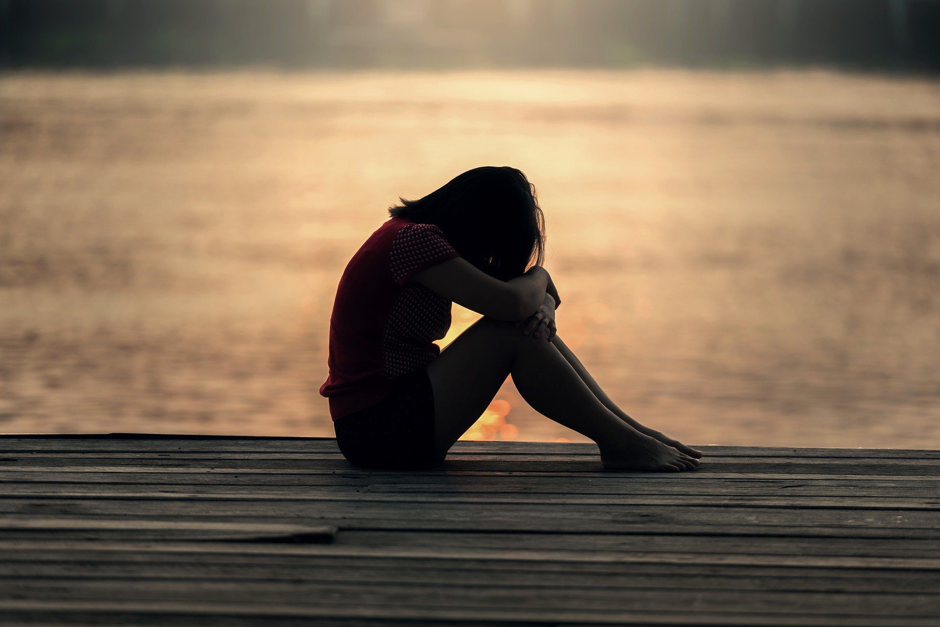 girl sitting on a dock with her arms wrapped around her knees with her head down