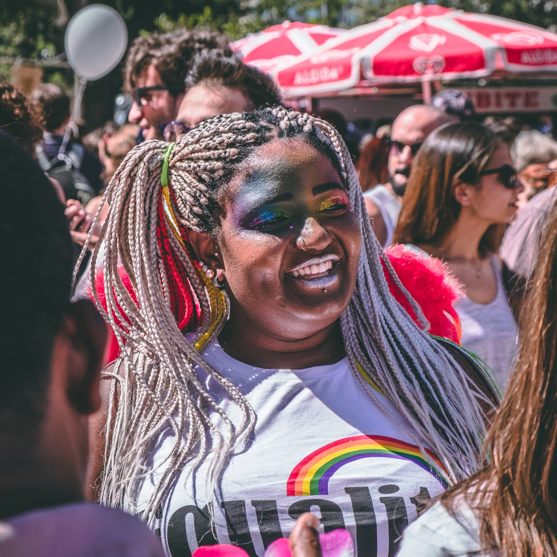 smiling woman wearing equality shit standing in the middle of a crowd