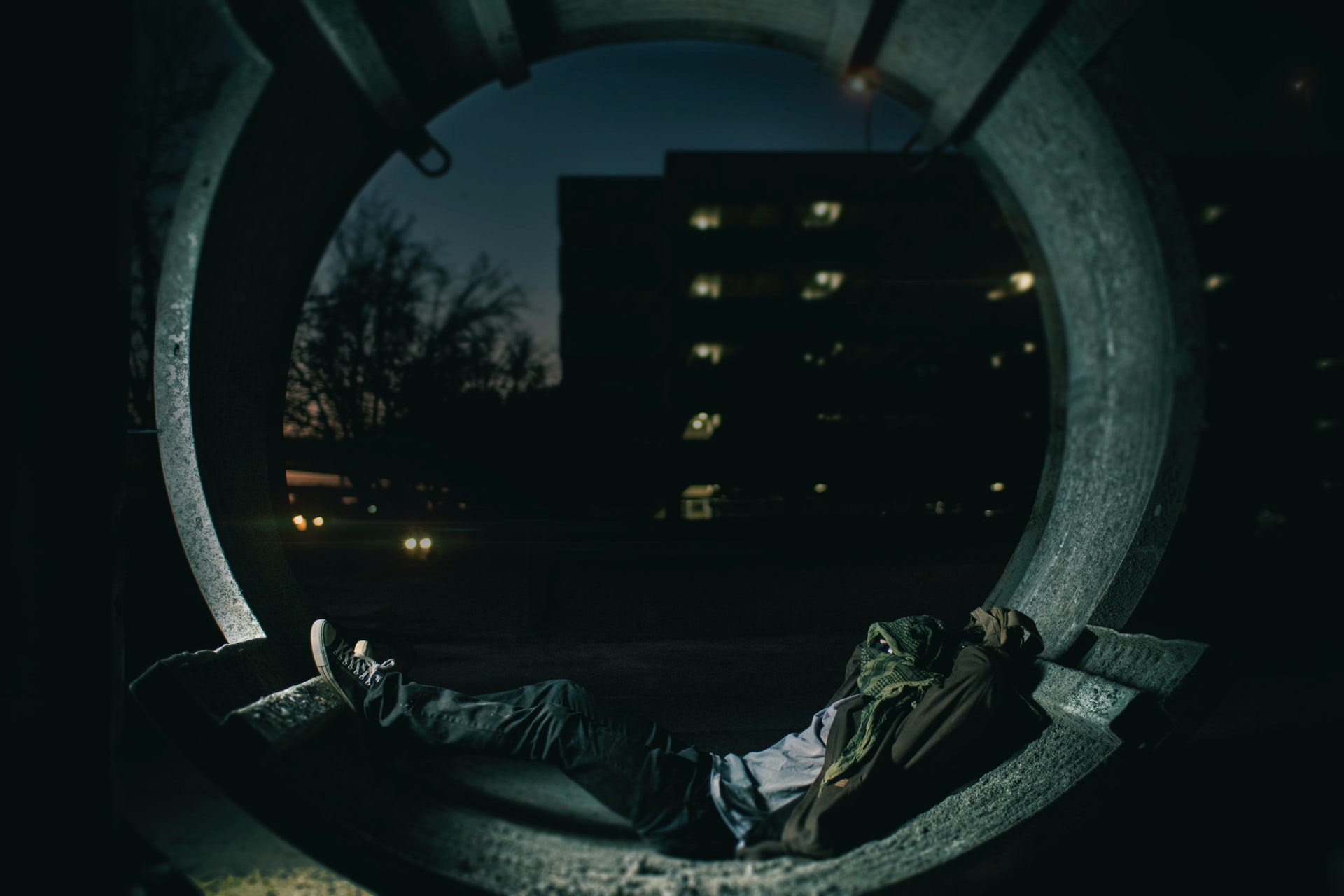 person laying inside drain pipe with building in the background