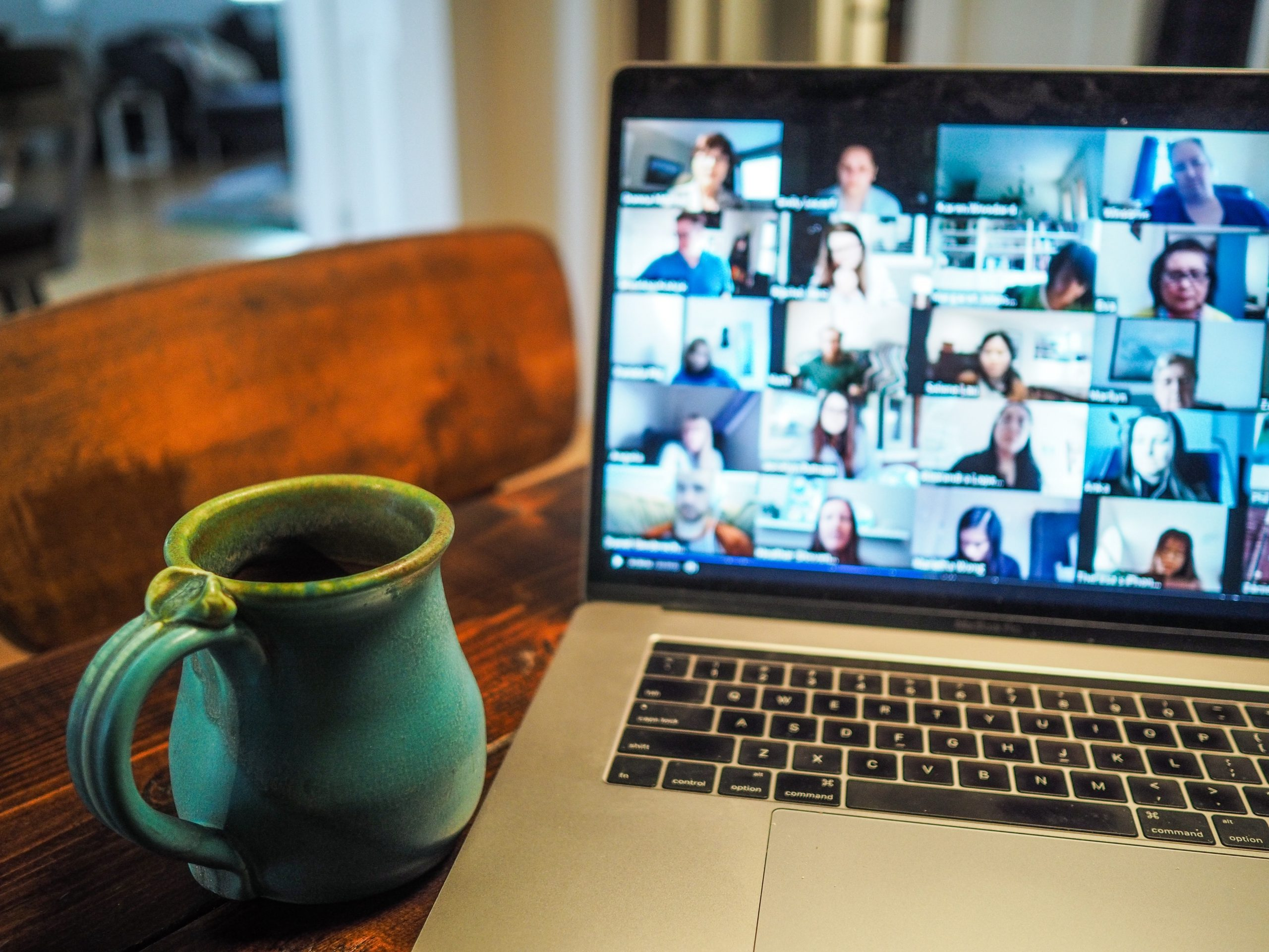 laptop with a zoom call next to a teal coffee mug on a wooden table