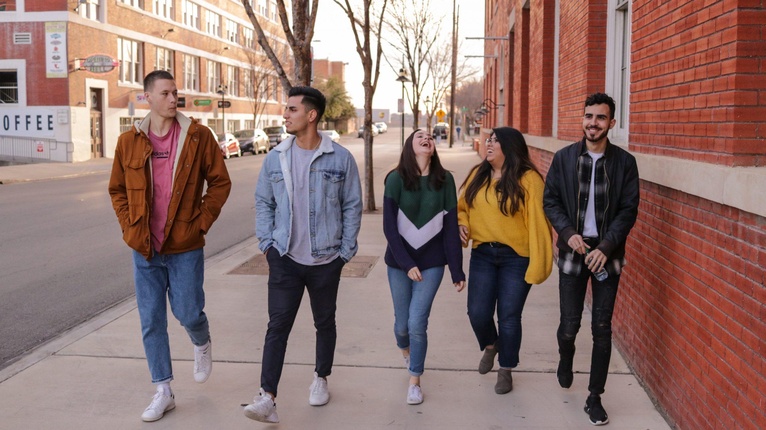 Image of 5 young people walking, talking, smiling, down an urban street.