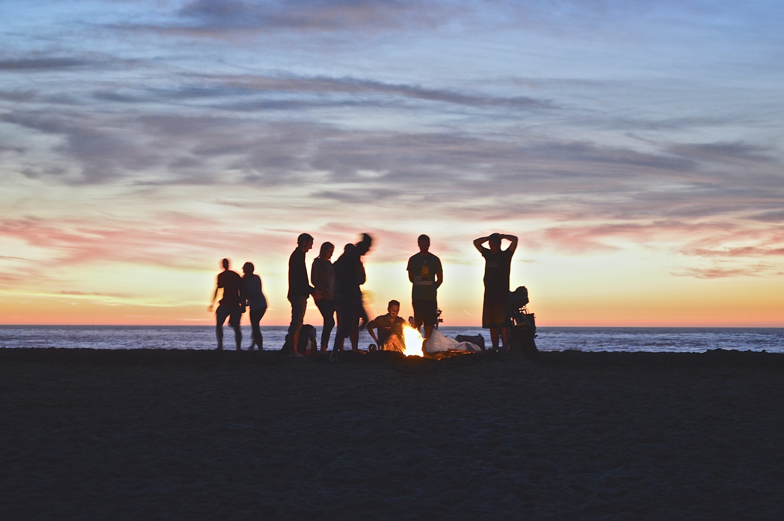 group of young people on the beach gathered around a bonfire at dusk