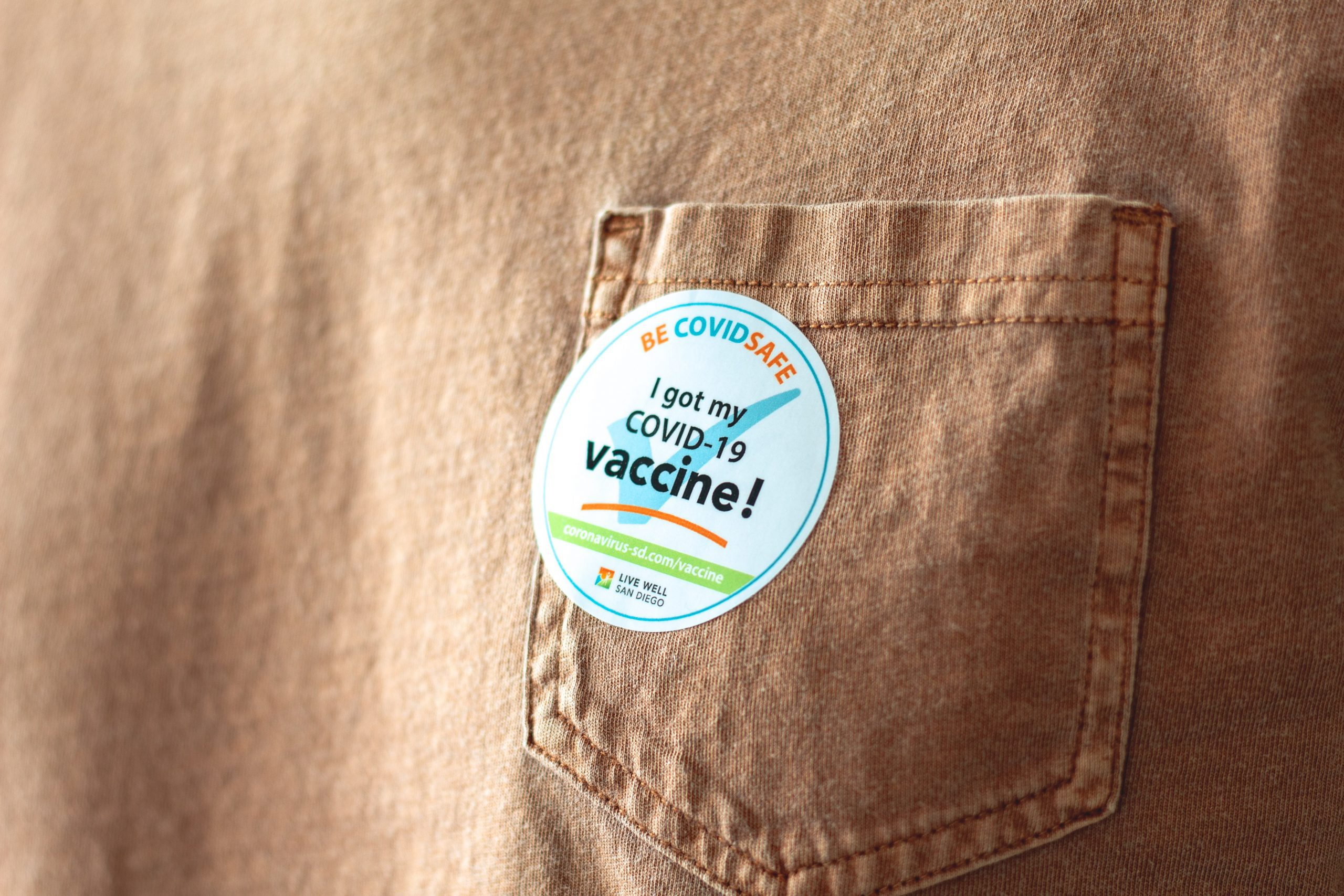 """Photograph of pocket on brown fabric with a sticker stating """"I got my COVID-19 vaccine!"""""""