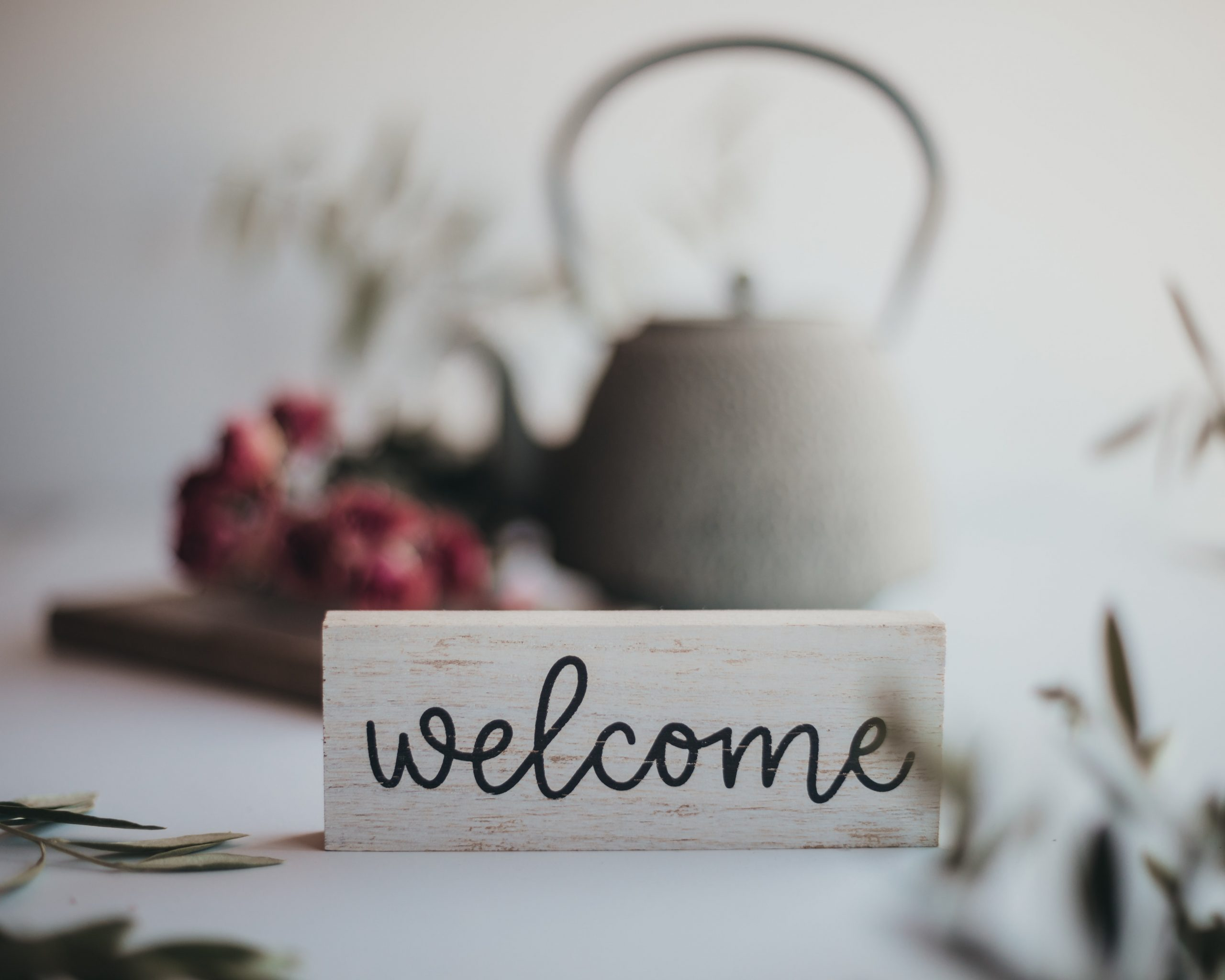 wooden welcome sign in cursive on a fake shrub background